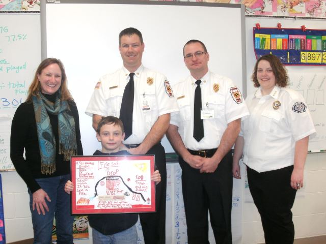 Darien fifth grader Jason Hines shows off his award-winning fire safety poster with, from left, Kathy Meulemans from the Wisconsin Alliance for Fire Safety, and Darien firefighters Dustin Ransom, Justin Schuenke and Stephaine Krueger.