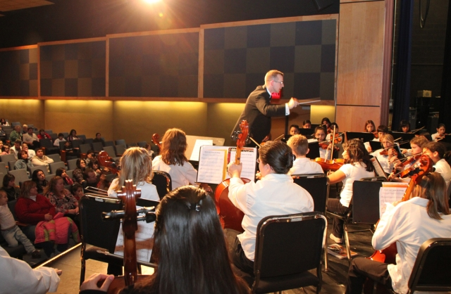 Tom May directs his elementary strings players at a past All District Orchestra Concert at DDHS.