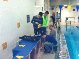 Woods teacher Mike Fellin works with students to assemble the new medals platform that will be used at DDHS home swim meets.