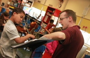 Elementary strings and band instructor Tom May gives a violin lesson to a Wileman student. (File photo)