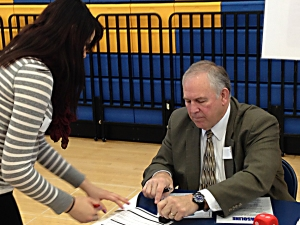 Superintendent Robert Crist checks off a student's budget worksheet after visiting his station.