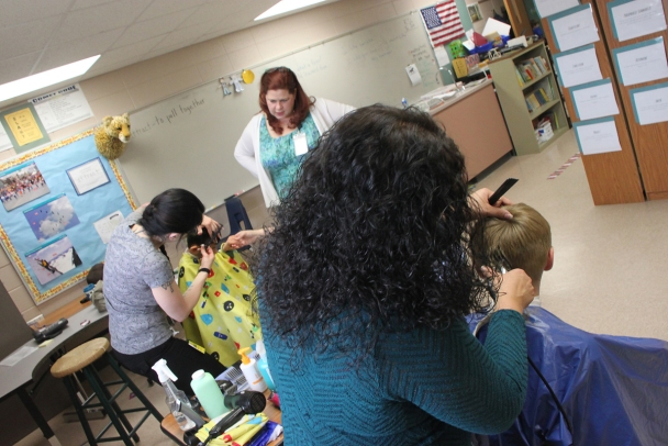 Stylists Katie Moser (left) and Dawn Salas cut the hair of two Turtle Creek students while Principal Rebecca Zahn looks on.