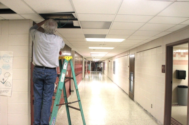 Workers install cabling for the additional security cameras being installed at Phoenix Middle School.